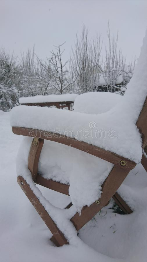 Snow on a wooden garden chair. Snowfall snowflakes white lying green dripping coated grass lawn yard blanket playing fun fun Christmas activity housing estate in stock image