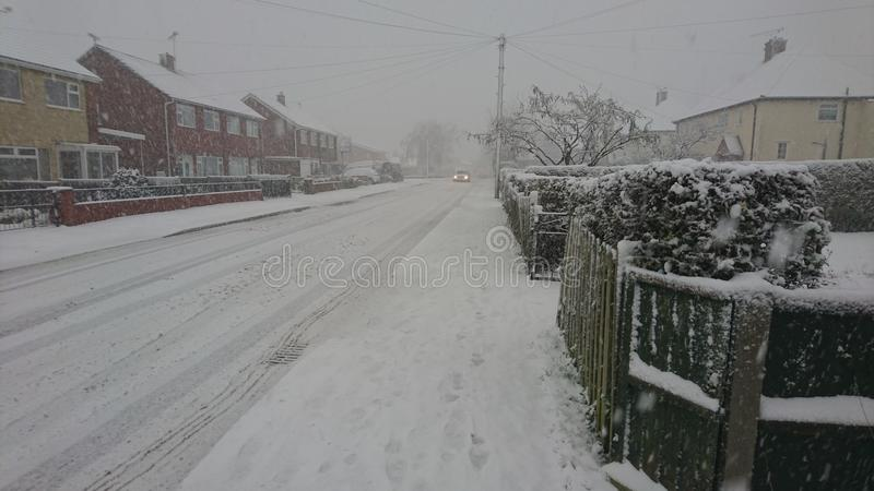 Car coming down a snowy village Street. Snowfall snowflakes white lying housing estate vehicle lights on headlights shining beaming glowing in the distance royalty free stock photo