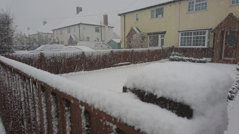 Snow on the fence on a village Street. Snowfall snowflakes white lying sitting frosty morning footprints slippy sliding garden front downfall powder town estate stock photography