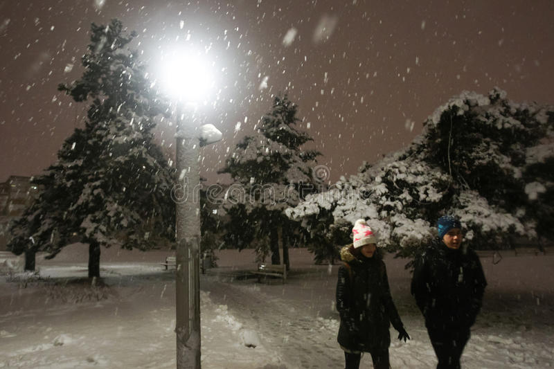 Snowfall on the streets of Velika Gorica, Croatia. VELIKA GORICA, CROATIA - JANUARY 13th, 2017 : A boy and a girl walking in the park covered with snow during stock images