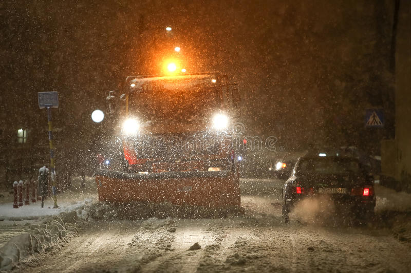 Snowfall on the streets of Velika Gorica, Croatia. VELIKA GORICA, CROATIA - JANUARY 13th, 2017 : Snowplow cleaning streets in the aggravated traffic due to stock photo
