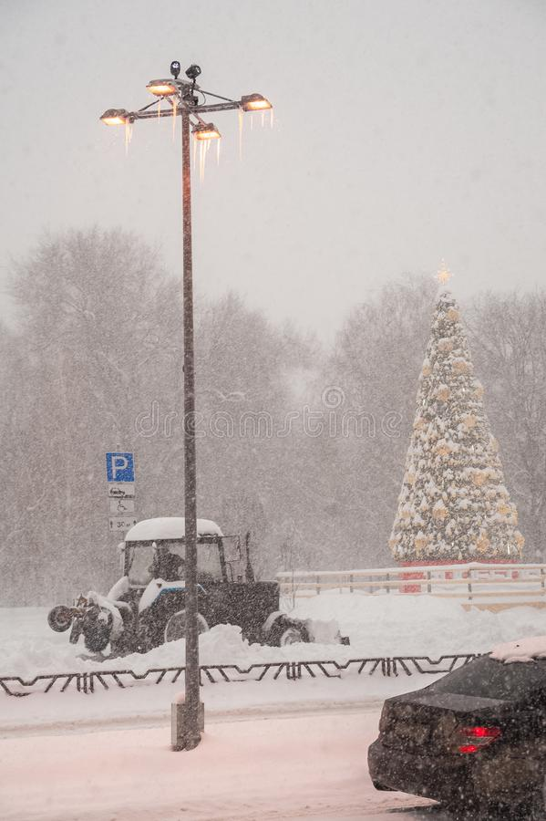 Snowfall in the winter. Snow blizzard in the city. Lantern, tree in the city, clearing the snow in the city stock image