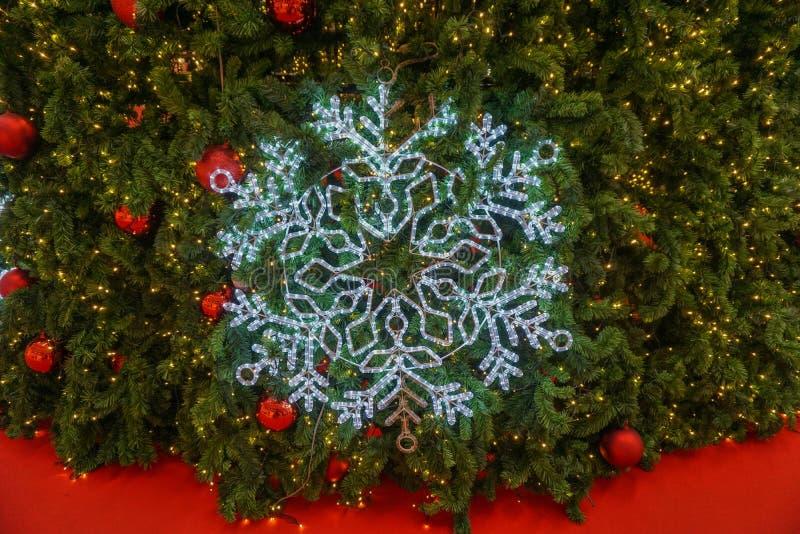 Snowflake και κόκκινες σφαίρες που κρεμούν στο χριστουγεννιάτικο δέντρο στοκ εικόνα