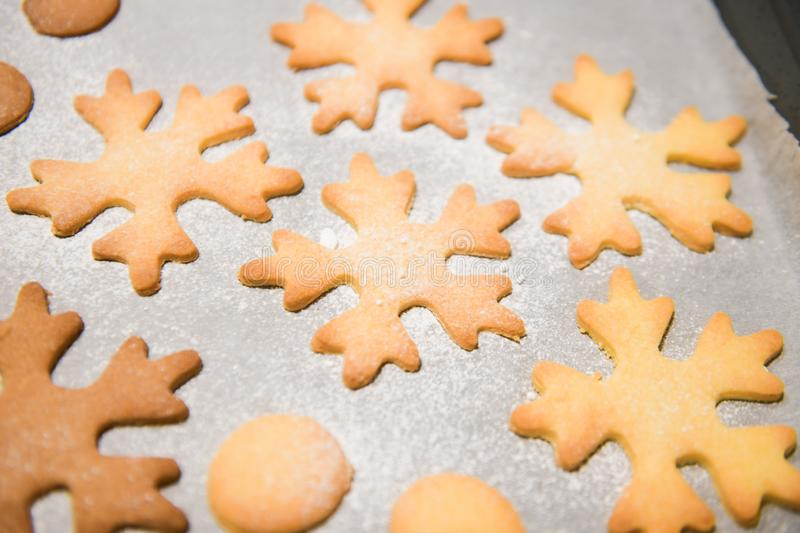 Snowflake cookies, baking on the baking sheet. Christmas gingerbread homemade. Merry Christmas card.  royalty free stock photo