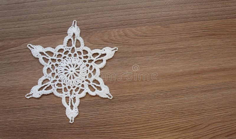 Snowflake knitted from white threads stock photo