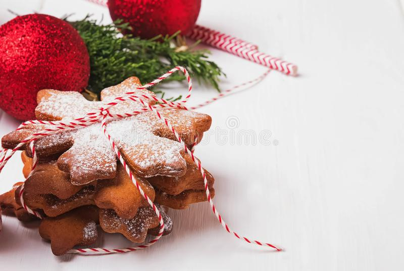 Snowflake shaped Christmas cookies sprinkled with icing sugar on the white table royalty free stock image