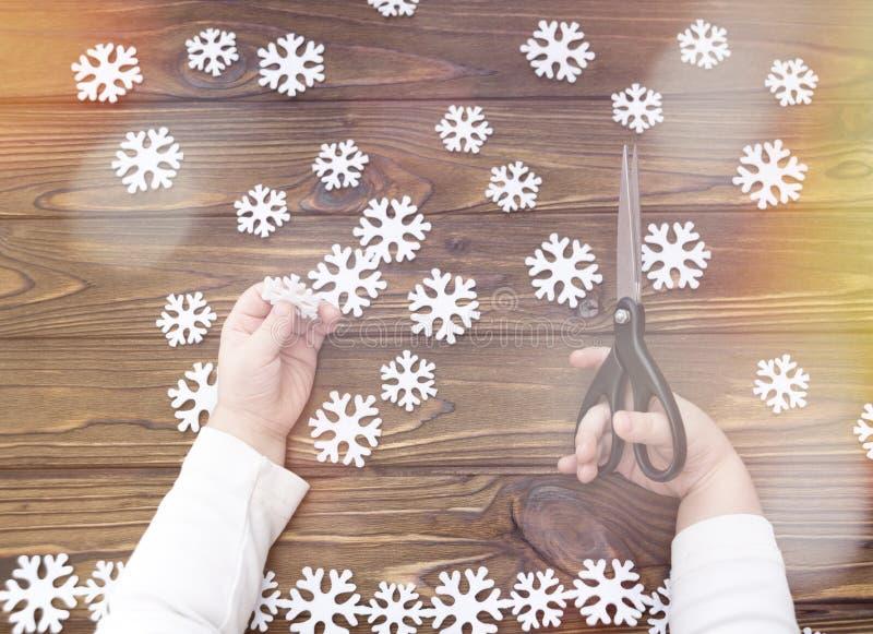 Snowflakes αισθητός, ψαλίδι, χέρια παιδιών ` s στο υπόβαθρο στοκ εικόνα