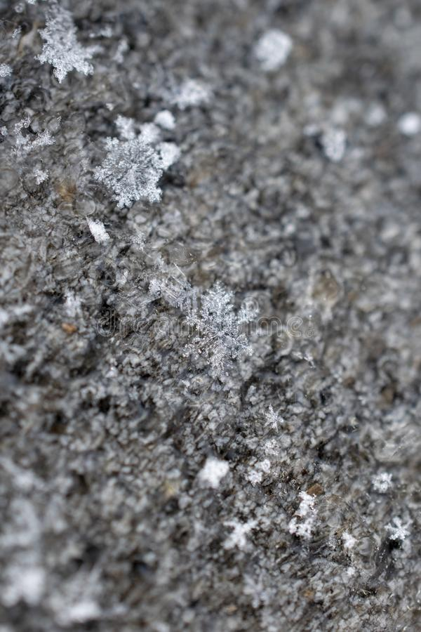 Snowflakes Melting Frosty Wood Winter Background. Frosty closeup of snowflake crystals frozen on a back porch in winter with rich texture and detail. Abstract stock photography