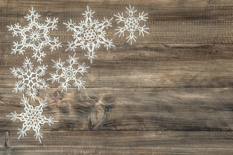 Snowflakes over rustic wooden background. Festive decoration stock photo