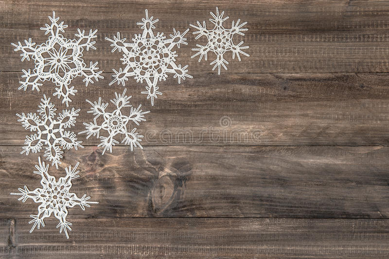 Snowflakes over rustic wooden background stock image