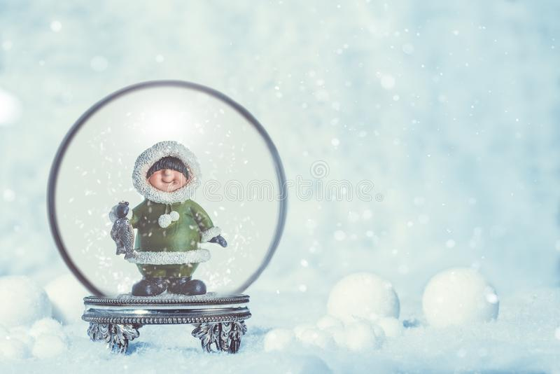 Snowglobe avec l'Esquimau à l'arrière-plan saisonnier image libre de droits