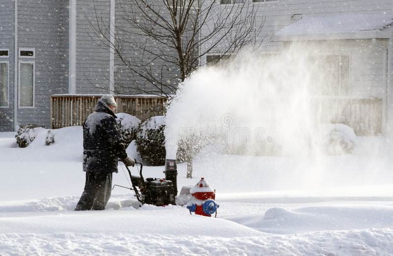 Snowing day worker blowing snow royalty free stock photo