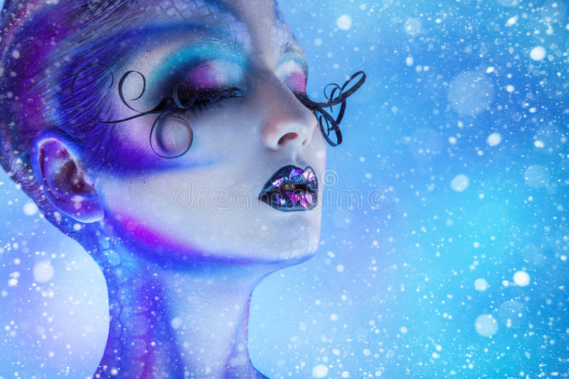 Snowing photo of beauty woman with closed eyes and creative body. Art in studio royalty free stock images