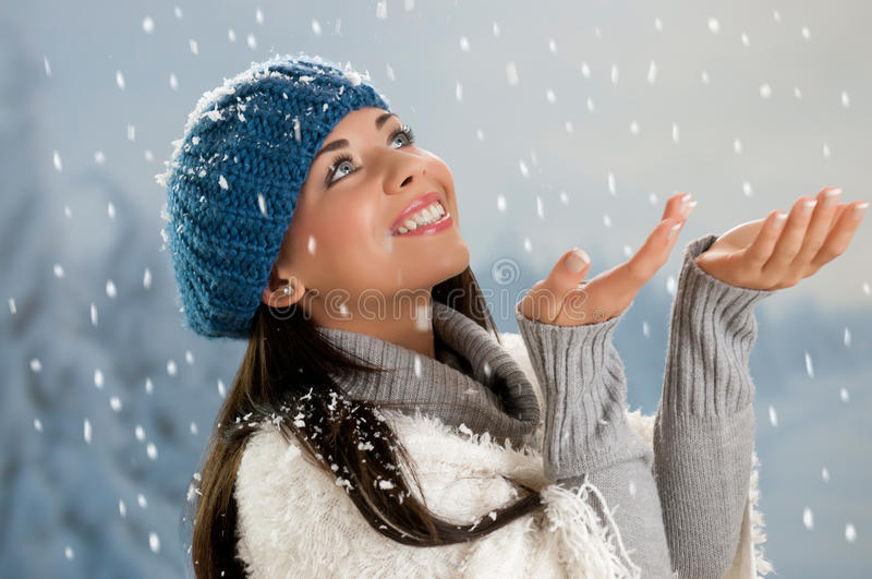 Snowing time in winter. Smiling beautiful young woman looking at falling snowflakes during a snowing winter day stock photo