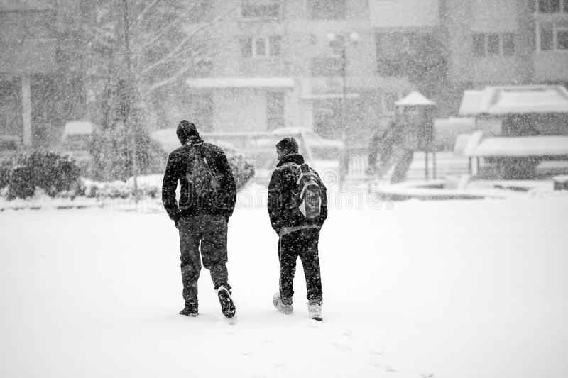 Snowing urban landscape with people. Passing by royalty free stock image