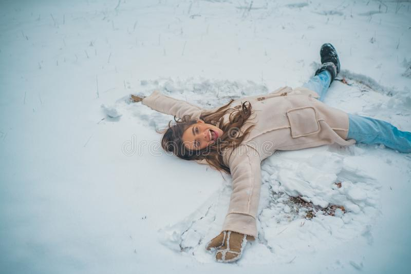 Snowing winter beauty fashion concept. Enjoying nature wintertime. Beautiful girl in snow. Winter mood. royalty free stock images