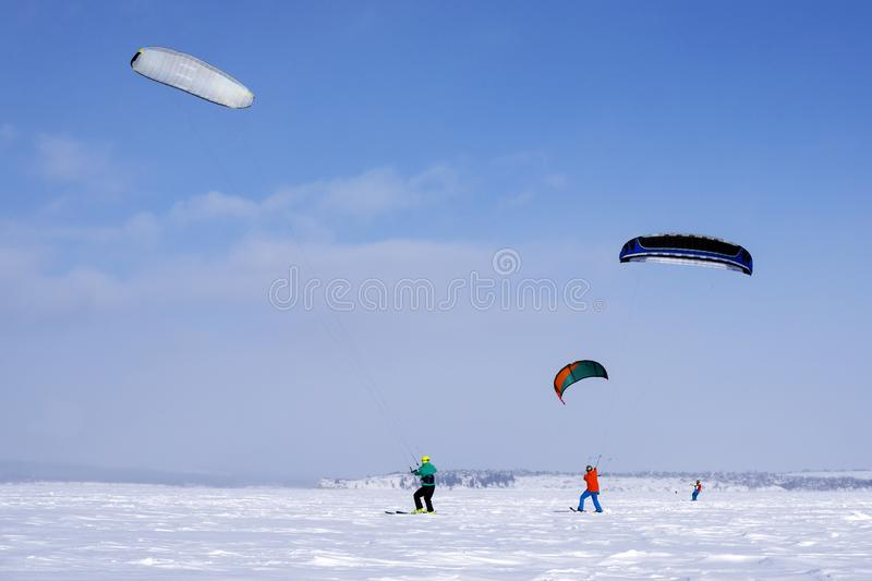Snowkiters ride on a winter clear day through the snowy plain royalty free stock photo