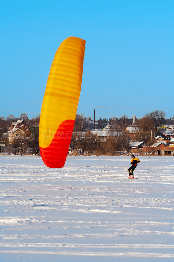 Snowkiting. Red and yellow power kite royalty free stock image
