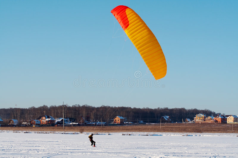 Snowkiting. Red and yellow power kite royalty free stock photography