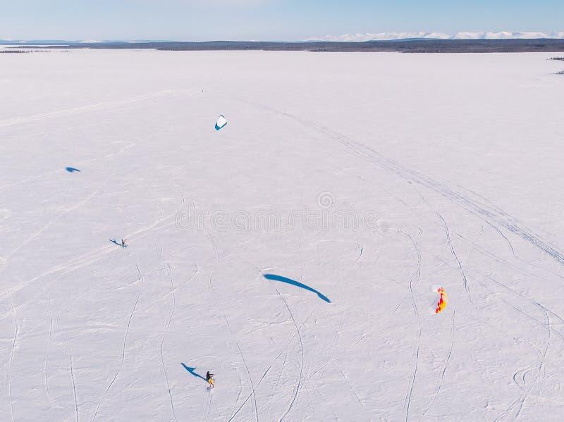 snowkiting Manlig idrottsman nen på bergskidåkning med drömdrakesnålskjuts på den djupfrysta sjön flyg- sikt royaltyfri foto