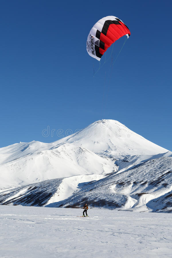 Snowkiting - sportsman glides on skis on background volcano. KAMCHATKA, AVACHA VOLCANO, RUSSIA - NOVEMBER 22, 2014: Kiteboarding or Snowkiting - sportsman glides stock image