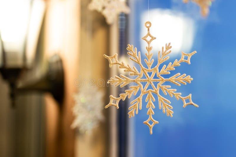 Snowlake da decoração do Natal e do ornamento do ano novo entregue perto da janela com a lâmpada morna lattern no fundo Cartão do foto de stock royalty free
