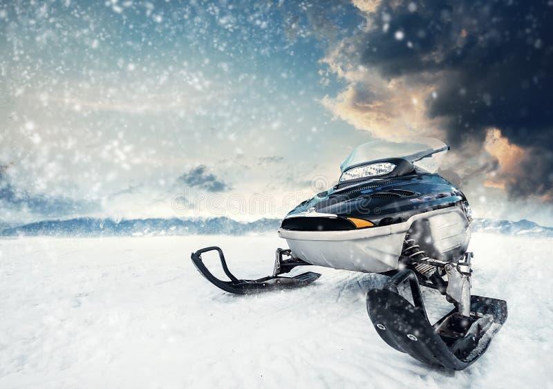 Snowmachine op de bergmeer bevroren oppervlakte met onweersbui betrekt op de achtergrond royalty-vrije stock afbeeldingen