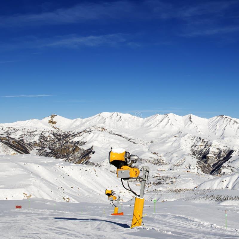 Snowmaking dans la pente de ski au jour du soleil image libre de droits