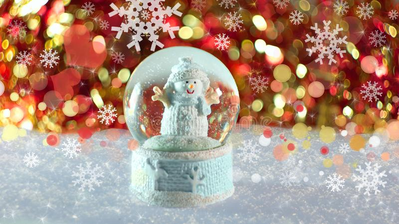 Snowman in a ball snow  natural festive red gold bokeh sequins tinsel royalty free stock photography
