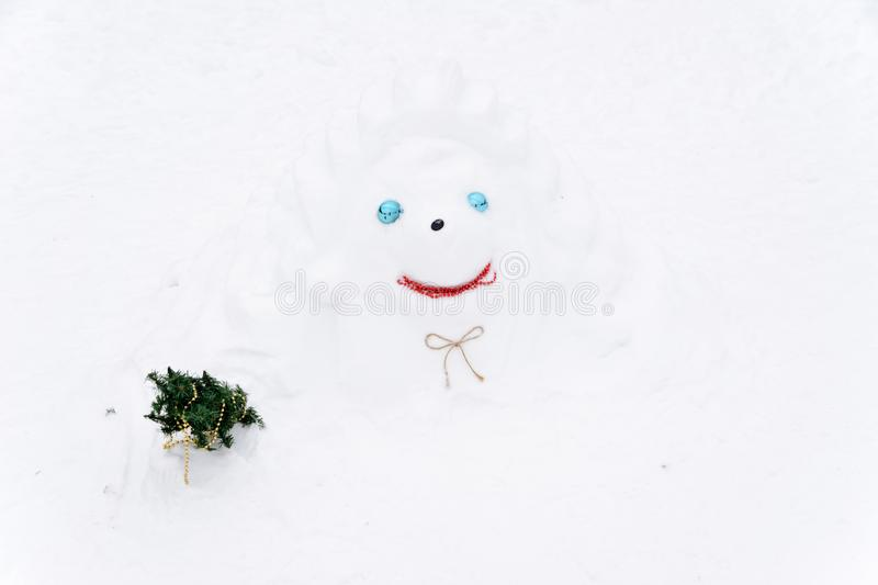 Snowman barely noticeable on the background of white snowdrifts in the winter landscape. A lot of snow stock photo