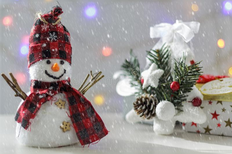 Snowman with christmas tree, gift boxes and christmas lights on the background. With snow effect royalty free stock photography