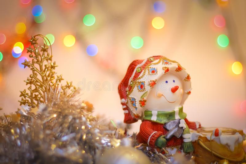 Snowman close-up on the background of blurry colored lights tinsel and Happy New Year royalty free stock photo