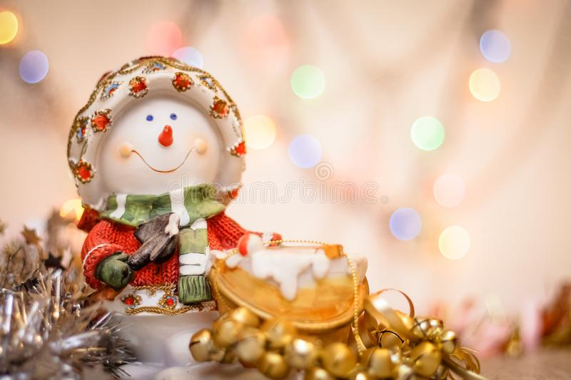 Snowman close-up on the background of blurry colored lights tinsel and Happy New Year royalty free stock photos