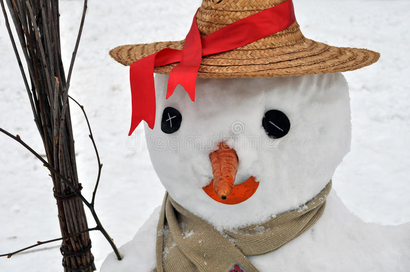 Snowman closed in straw hat and scarf. And holding broom royalty free stock photos