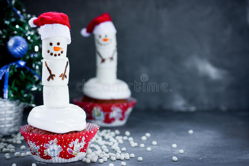 Snowman cupcake Christmas treats. Snowman cupcake - Christmas cupcakes decorated with funny marshmallow snowman royalty free stock image