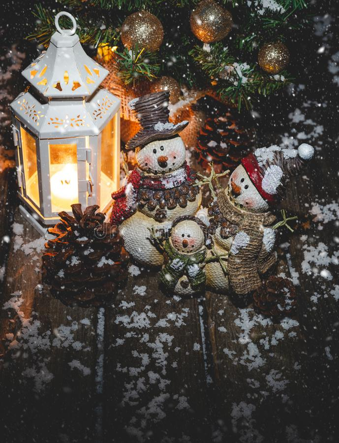 Snowman Family With Glowing Lantern and Christmas Tree stock photography