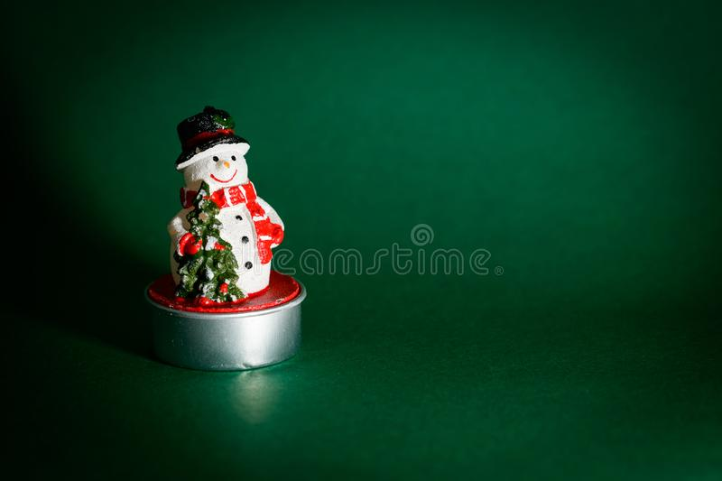 Snowman figurine isolated on green background stock photography