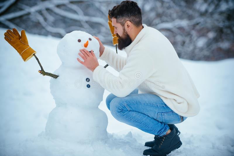 Snowman and funny bearded man in the snow. Man playing with Snowman - isolated on snow background. Joyful Handsome young stock photos
