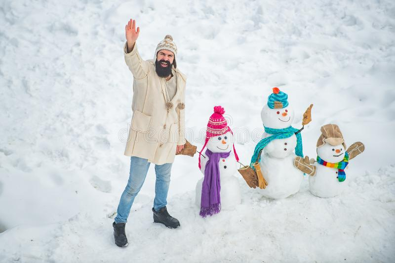 Snowman and funny bearded man in the snow. Winter man. Christmas winter people. Winter portrait of young handsome royalty free stock photo