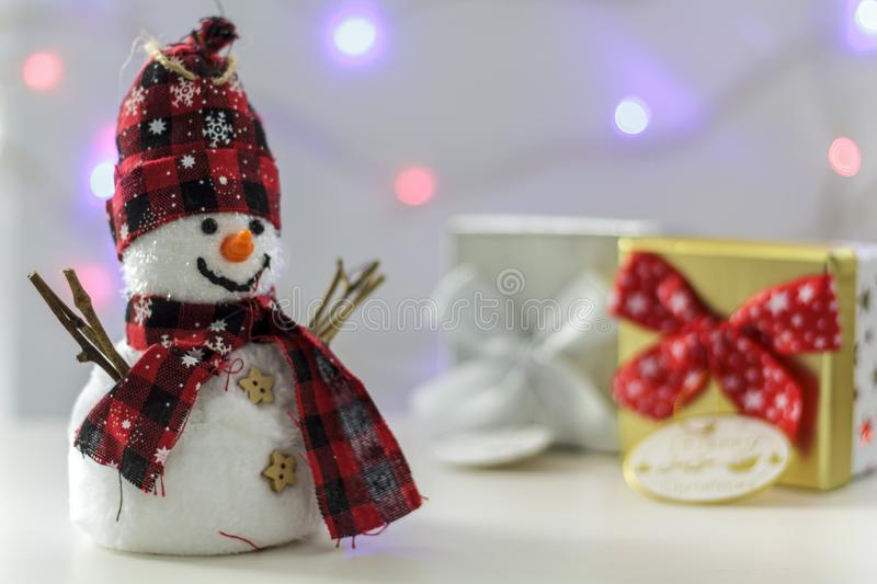 Snowman with gift boxes and christmas lights on the background stock photo