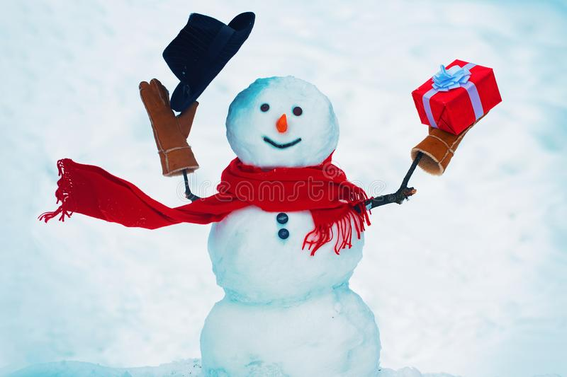 Snowman with gift outdoor. Merry Christmas and happy New Year greeting card with copy-space. royalty free stock photos