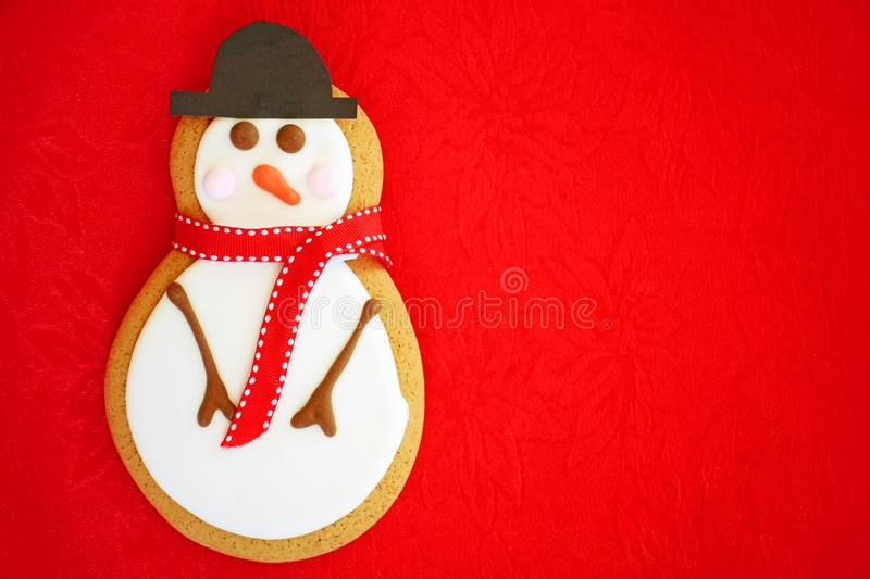Snowman gingerbread cookie on red. Snowman gingerbread man in jaunty hat and scarf on vivid red background. Horizontal format in flat lay stock photo