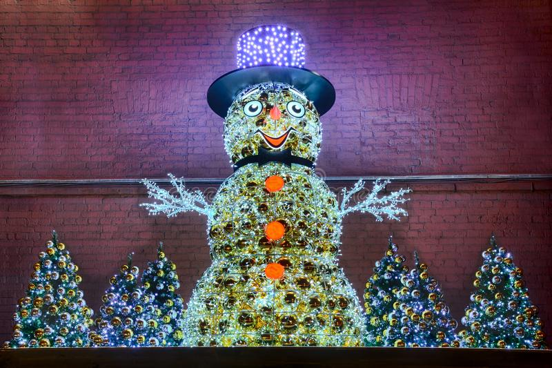 Snowman in Hat with Christmas Trees at the Wall of the Power Plant No 1 stock photography