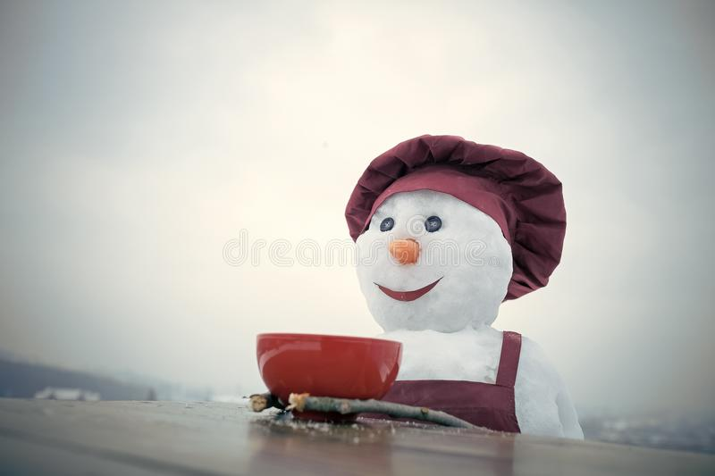 Snowman is having breakfast. New year snowman in cook hat. Happy holiday celebration. Christmas food cooking. Snowman chef in winter with kitchen plate. Xmas stock images