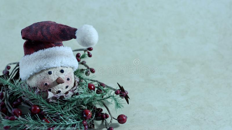 Smiling snowman head with a hat on a cream background royalty free stock photo