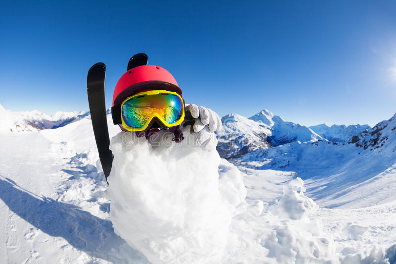 Snowman in helmet and mask against mountain scene stock photo
