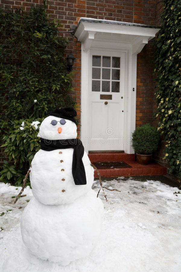 Snowman and house stock photography