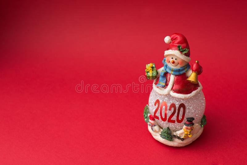 Snowman isolated on red background. Snowman with scarf and red cap 2020 stock photo