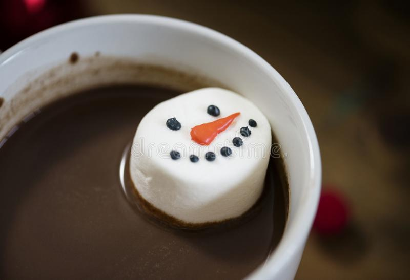 Snowman marshmallow dipped in hot chocolate royalty free stock photo