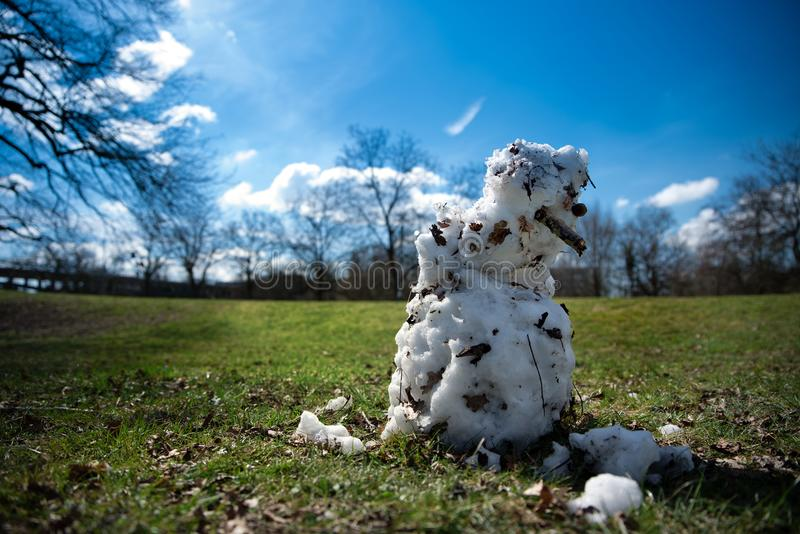Snowman melting in spring sun stock images